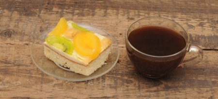Close-up of glass cup of coffee and apricot cake on wooden table photo