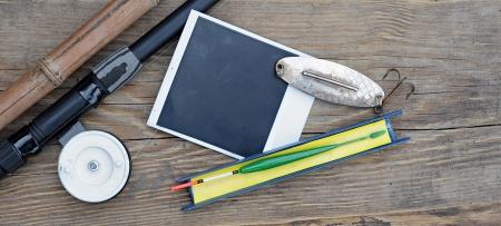 Fly fishing rod with  photo frame on wood background photo