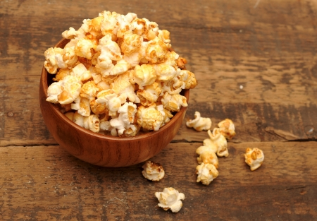 bowl of popcorn: popcorn in brown bowl on wooden table  Stock Photo