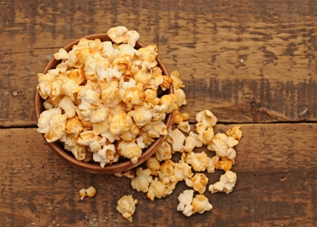 popcorn in wooden bowl on wooden table  photo
