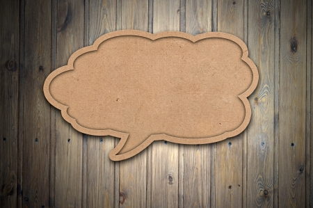 blank recycled paper speech bubble on wood background  photo