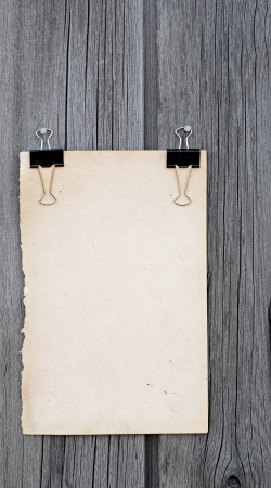black clip and old blank note paper hang on wood panel  photo