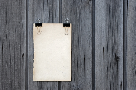 black clip and old blank note paper hang on wood panel Stock Photo - 14409822