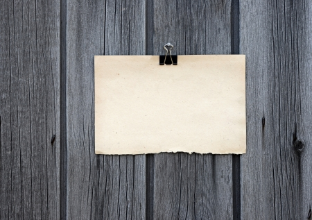 black clip and old blank note paper hang on wood panel Stock Photo - 14409821