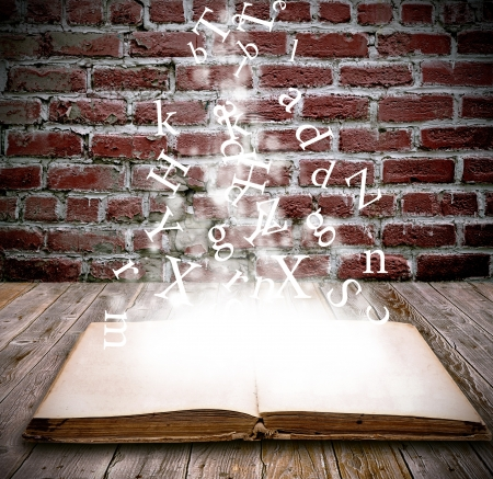 An open book with letters falling into the pages  Stockfoto