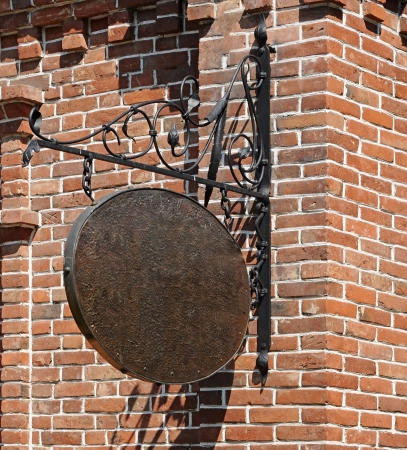 Blank, dark, shop sign hanging in a wrought iron bracket from a brick wall  photo
