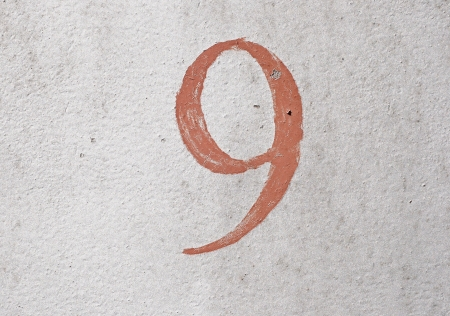 9 - old brown handwritten number over grunge silver background photo