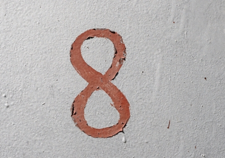 8 - old brown handwritten number over grunge silver background photo