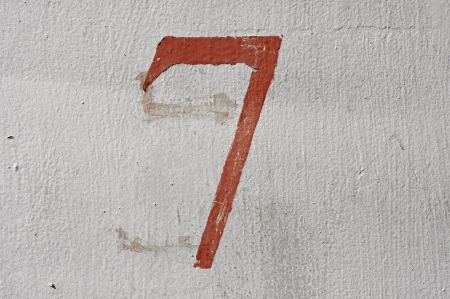 7 - old brown handwritten number over grunge silver background photo
