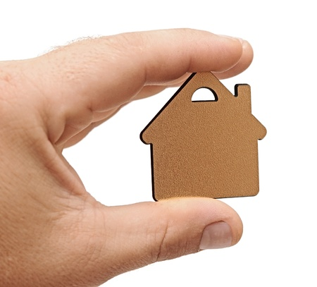 golden metallic small house in human hand photo