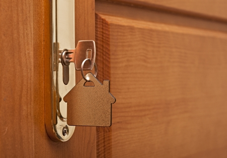 door key: A key in a lock with house icon on it  Stock Photo