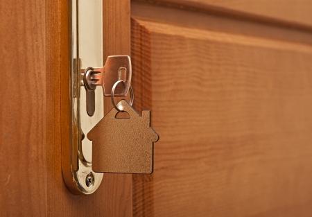 rental house: Una llave en una cerradura con casa icono sobre la misma Foto de archivo