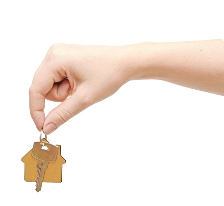 hand with chrome house key isolated on white Stock Photo - 15127432