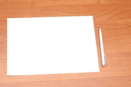 Blank sheet of paper with pen on wooden background  photo