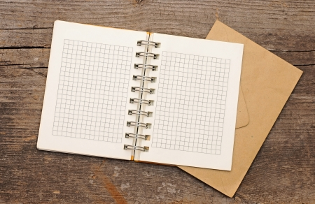 note book with old envelopes on wooden background. With copy space photo