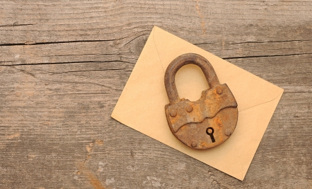 Old padlock on yellow envelope over  wooden background.With copy space photo