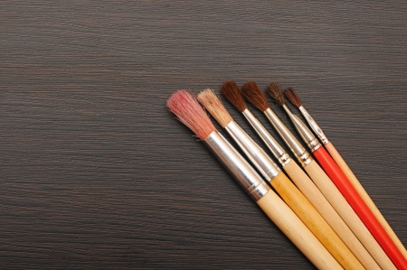 Paint brushes on dark wooden background photo