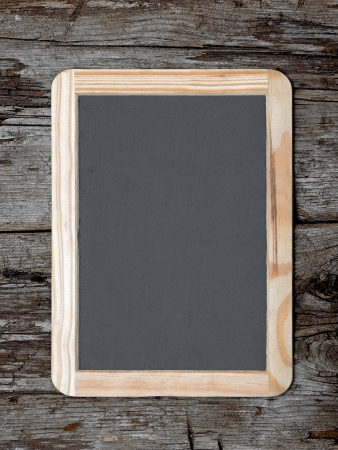 Grunge small blackboard hanging on wooden wall as a background for your message photo