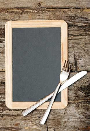 cucina antica: Lavagna Menu giace sul tavolo di legno con coltello e forchetta Archivio Fotografico
