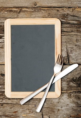 Menu blackboard lying on wooden table with knife and fork