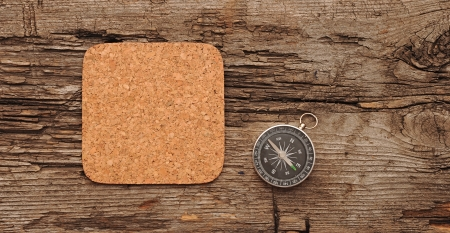 noteboard: cork memory board and compass on old wooden background Stock Photo