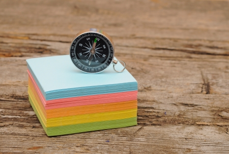 notelet: colorful post it note block with compass on wood table Stock Photo