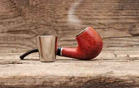 pernicious: stainless glass of cognac and tobacco pipe on old wooden background.  Stock Photo