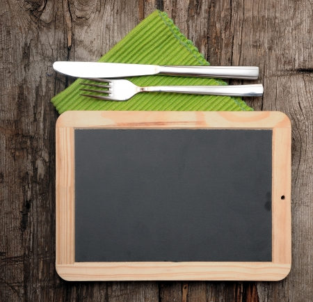 Menu blackboard lying on old  wooden table with knife and fork Stockfoto