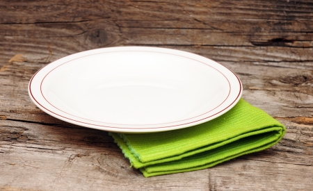 on the tablecloth: Empty white plate on wooden table