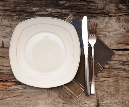 Empty dish, knife and fork and brown napkin on old wood table  Stock Photo - 16031895