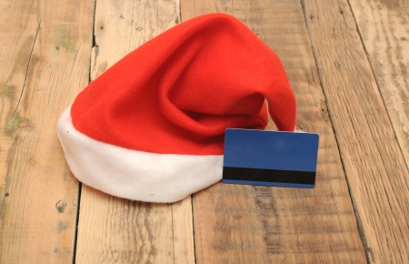 Santa Claus hat with a blank credit card on wooden background photo