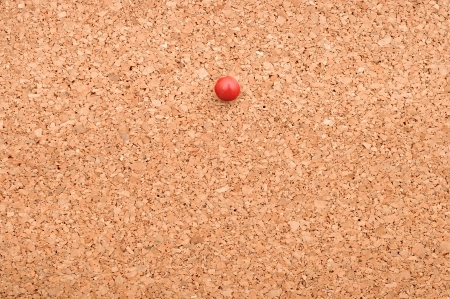 red pushpin on a cork board photo