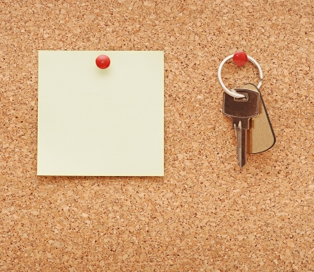 clean post-it note and home keys stuck to a cork notice board photo