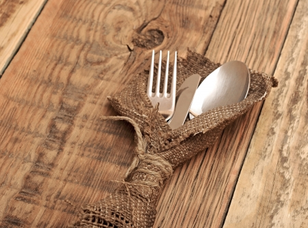spoon, knife and fork in rough old sacking over wood with sample text photo