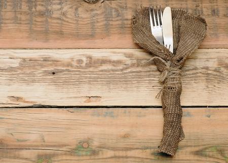 cuchillo y tenedor en áspero antiguo arpillera sobre madera Foto de archivo