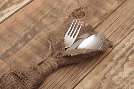 knife and fork in rough old sacking over wood photo