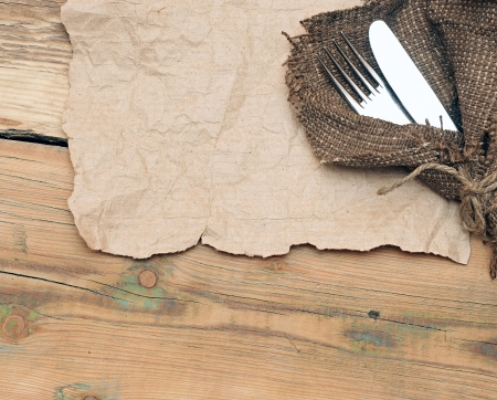 A place setting with silver fork and knife on old sacking texture  photo