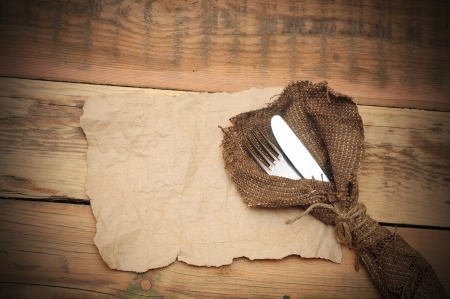 grunge silverware: knife and fork in rough old sacking on blank paper over wood