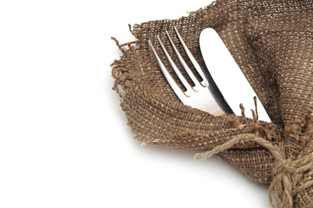 A place setting with silver fork and knife in textile napkin over white with sample text  photo