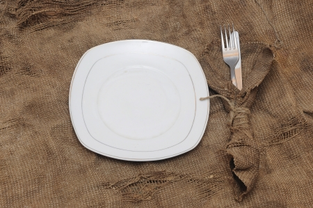 empty white plate fork and knife on brown sacking texture Stock Photo - 16185013