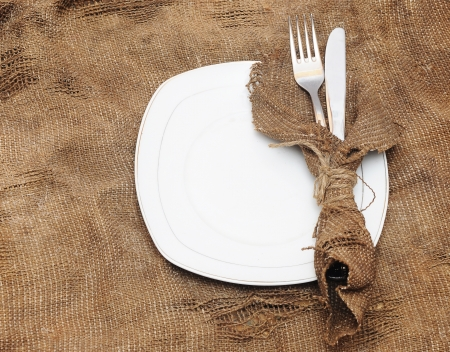 empty white plate fork and knife on brown sacking texture photo