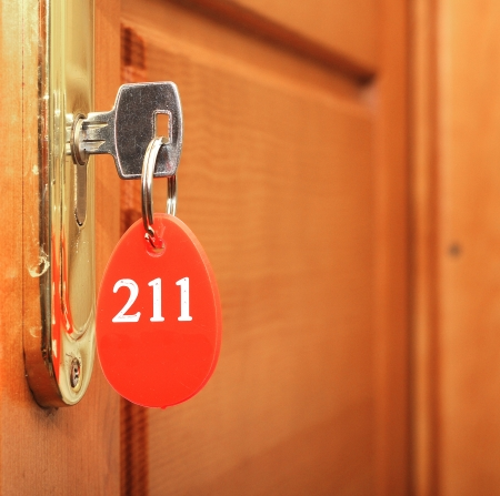 Door handles on wood wing of door and key in keyhole with numbered label Stock Photo - 16271790