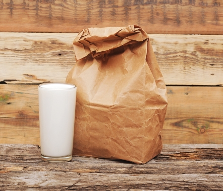 Paper lunch bags with glass milk over wooden background photo