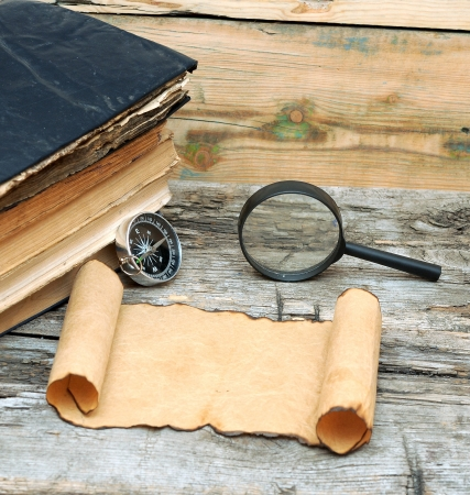 Stack of antique books with compass, magnifying glass and paper scroll on wood background photo