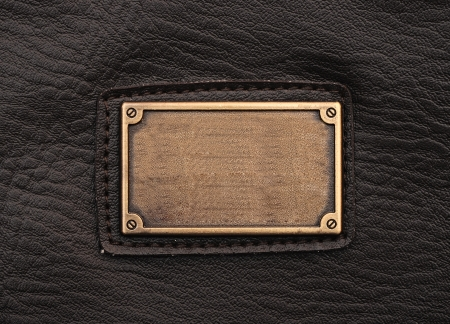 metal label on old black leather background photo