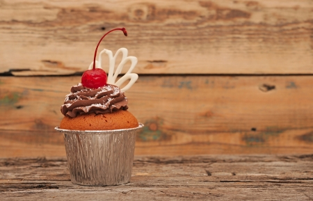 defocussed: Chocolate cherry cupcakes on old wooden background Stock Photo