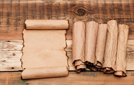 blank old sheet paper with pile scrolls on old wooden background photo