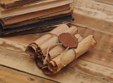 Mucchio di vecchi libri e di scorrimento su sfondo di legno Archivio Fotografico - 16485342