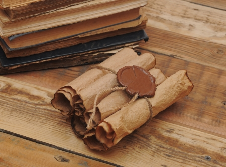 Pile of old books and scroll on wood background photo