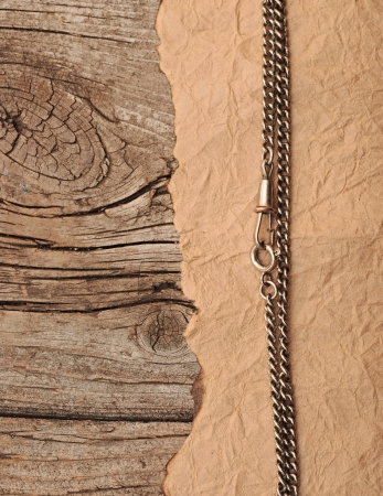paper vintage and metal chain on wood background photo